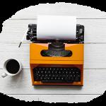 Orangefarbene Schreibmaschine, daneben eine Kaffeetasse
