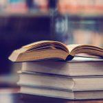 Aufgeschlagenes Buch auf einem Bücherstapel