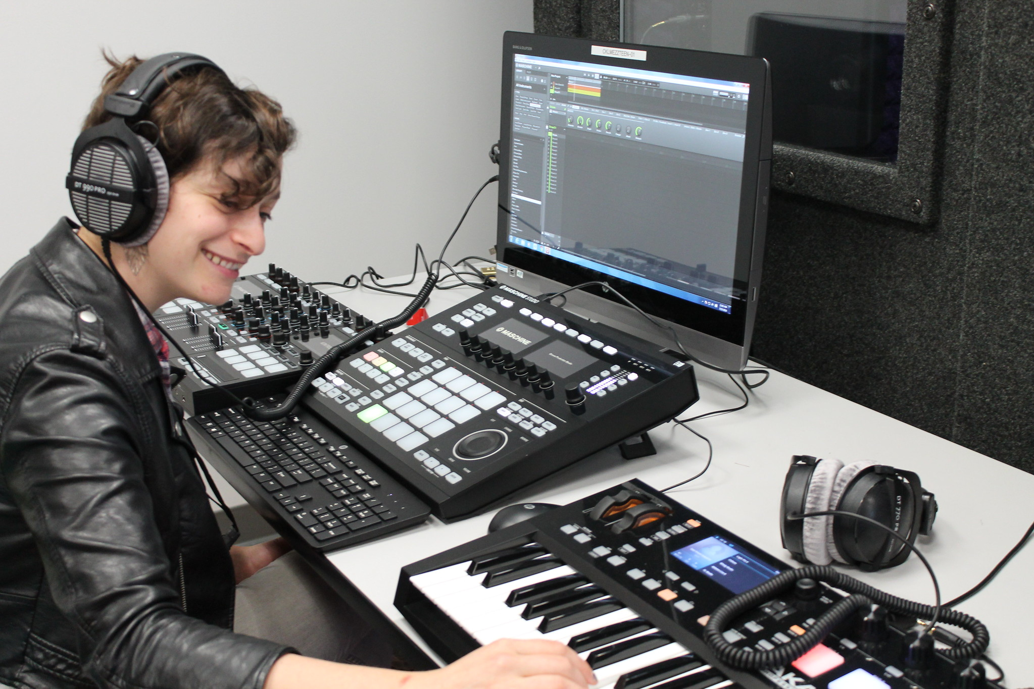 Frau am Computer mit Kopfhörern auf, Hände auf einem Mischpult, zur Bebilderung von OER-Tracks.